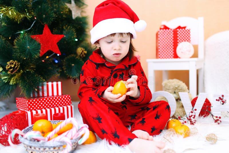 Den älskvärda pysen i jultomtenhatt med tangerin sitter nära Christma arkivbilder