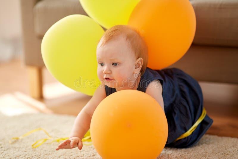 Den älskvärda rödhåriga mannen behandla som ett barn flickan med hemmastadda ballonger royaltyfri foto