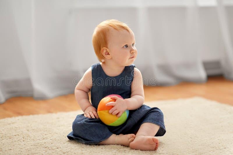 Den älskvärda rödhåriga mannen behandla som ett barn flickan med leksakbollen hemma arkivbild