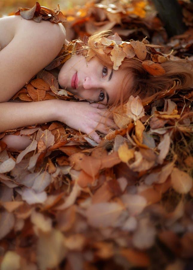 Den älskvärda unga flickan ligger på höstsidor som är dolda med kulöra höstliga sidor, med fritt utrymme för din text royaltyfri foto