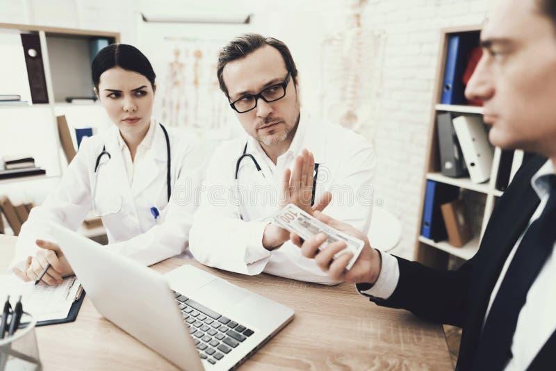 Den ärliga doktorn och sjuksköterskan vägrar att ta mutan från patient i medicinskt kontor arkivfoto