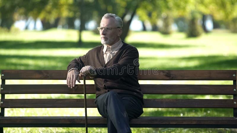 Den åldrades mannen med den gå pinnen som vilar på bänk parkerar in och att tycka om vårnaturen arkivfoto