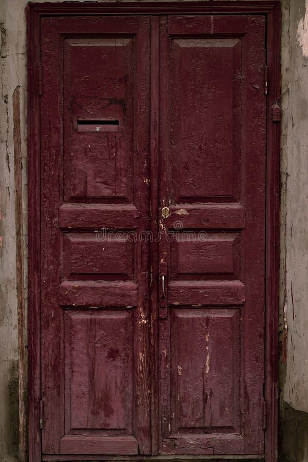 Den åldrades trädörren målade rödbrunt Tappninghusfasad med en dörr Vinous textur för trä av en dörr Gammal burgundy grungetextur royaltyfria foton