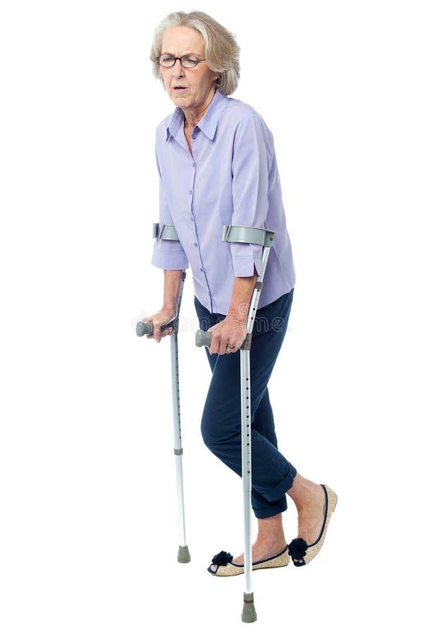 Den åldriga kvinnan smärtar in att gå med kryckor arkivfoto