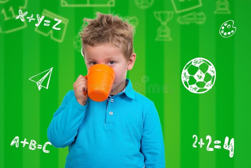 Den 3-åriga pojken i blåa punkter dricker från en råna fotografering för bildbyråer