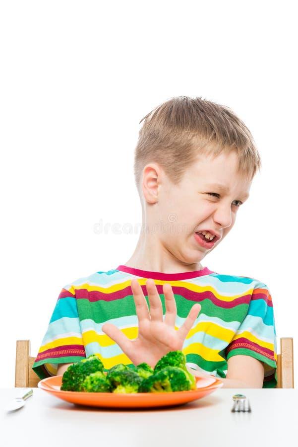 den 10-?riga pojken v?grar en platta av broccoli f?r lunch, begreppsfotoungar royaltyfri foto