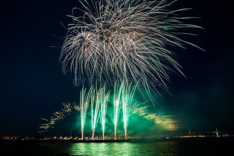 Den åtskilliga färgrika fyrverkeribristningen i natthimlen med ljus skuggar över havet royaltyfria bilder
