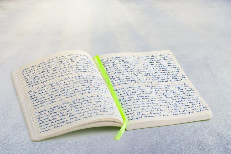 Den öppna anteckningsboken med handskriven lorem ipsumtext och bandet bokar fotografering för bildbyråer
