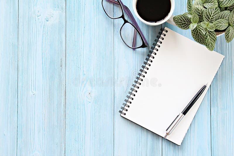 Den öppna anteckningsboken med tomma sidor, kaffekoppen och glasögon på träskrivbordtabellen, den bästa sikten eller lägenheten l fotografering för bildbyråer