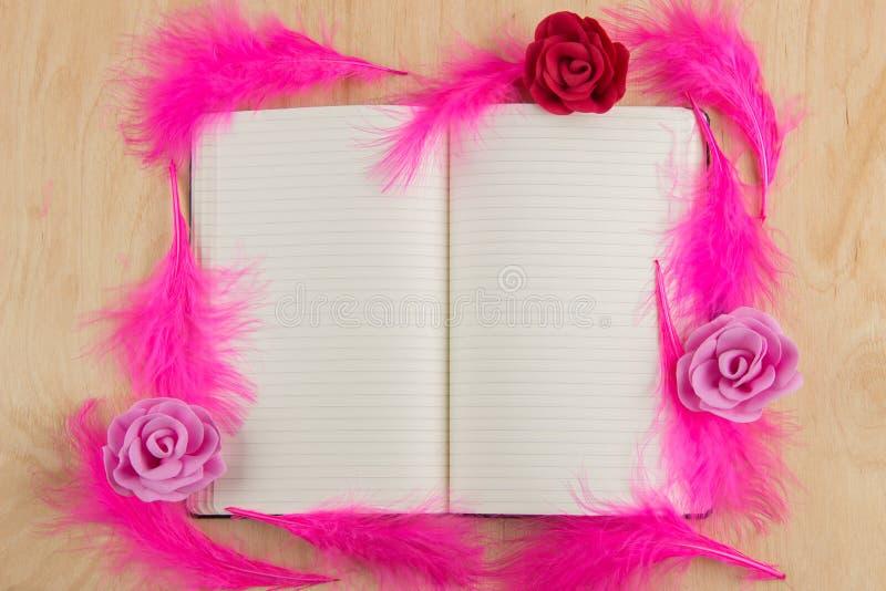 Den öppna anteckningsboken med vita sidor och rosa färger befjädrar på en träflik arkivfoto