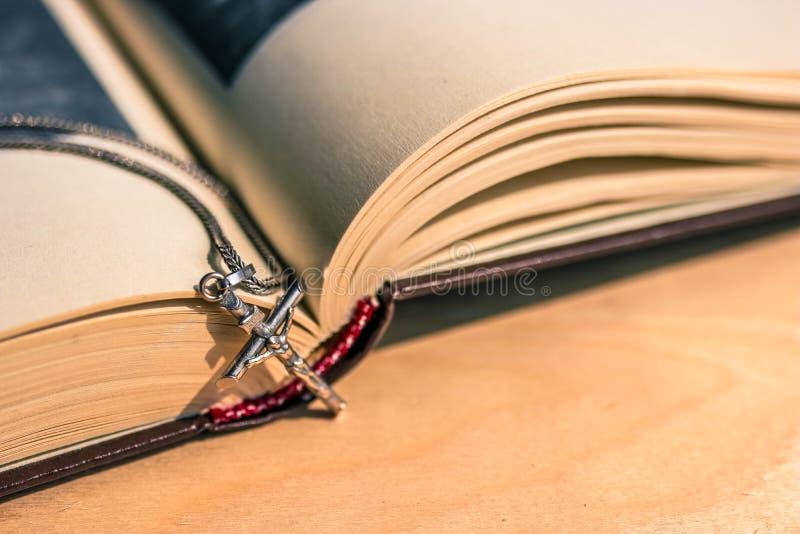 Den öppna bibelboken på trätabellen och försilvrar kedjan med försilvrar argt slut upp sikt fotografering för bildbyråer