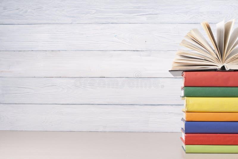 Den öppna boken, inbunden bok bokar på trätabellen sax och blyertspennor på bakgrunden av kraft papper tillbaka skola till Kopier arkivbild