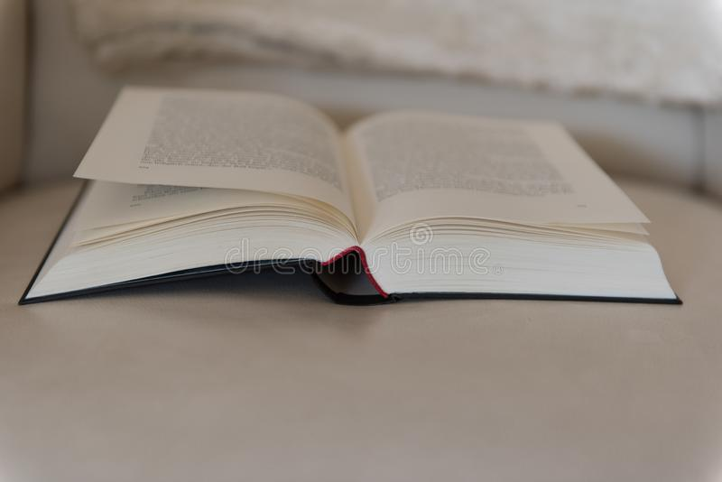 Den öppna boken ligger på en läderstol fotografering för bildbyråer