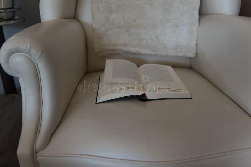 Den öppna boken ligger på en läderstol royaltyfria foton