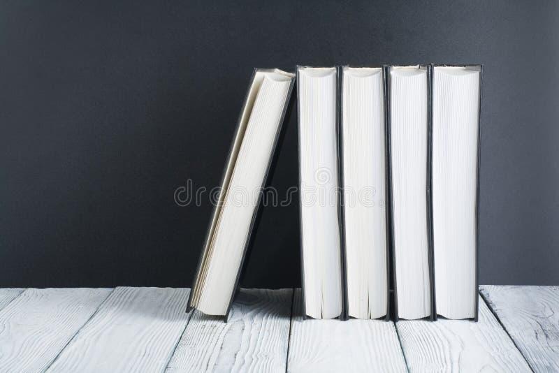 Den öppna boken, svart, Whitel bokar på trätabellen, svartbrädebakgrund tillbaka skola till Utbildningsaffärsidé arkivbilder