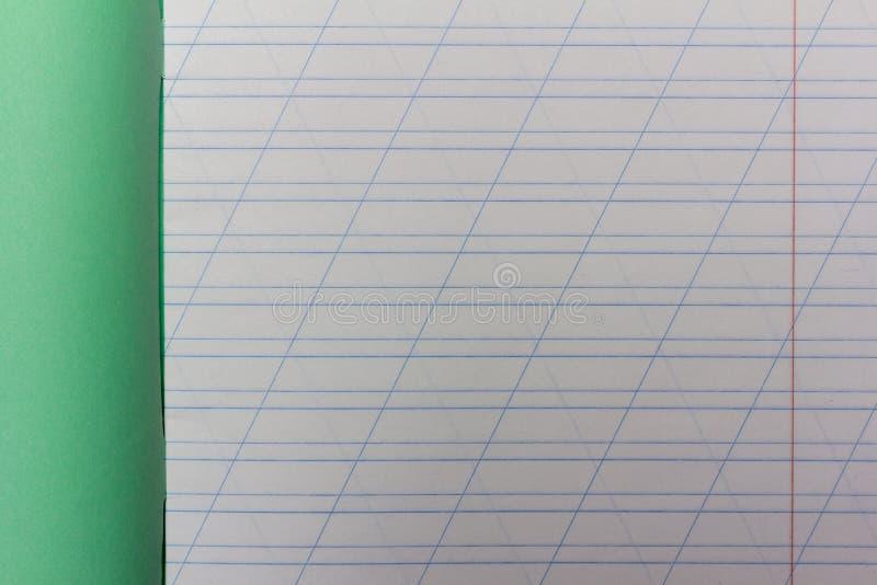 Den öppna skolaanteckningsboken i en smal linje med ett snedstreck för att lära stavning, förlöjligar upp arkivfoton