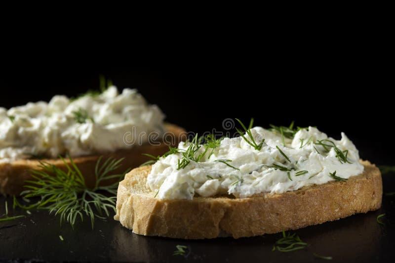 Den öppna smörgåsen med rostat bröd och homandeost lagar mat med grädde med nytt dil arkivfoton