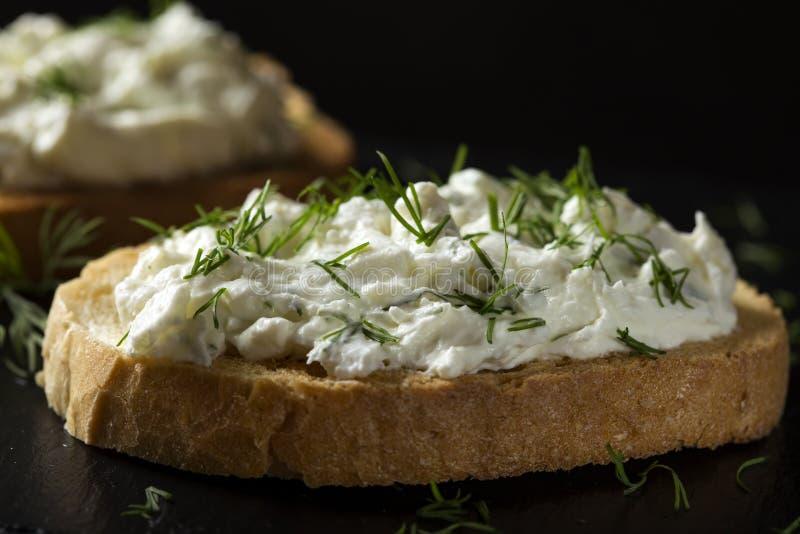 Den öppna smörgåsen med rostat bröd och homandeost lagar mat med grädde med nytt dil arkivbilder