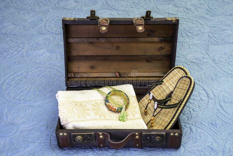 Den öppna tappningresväskan packade med handduken, det tropiska armbandet, hals arkivbild