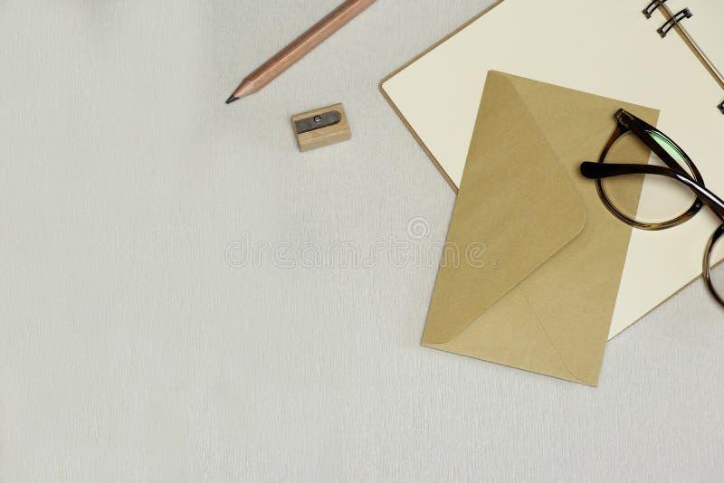 Den öppnade anteckningsboken, blyertspenna, vässare, kuvert, anblickar på den vita bakgrunden royaltyfria foton