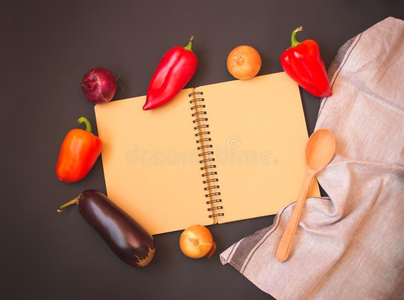 Den öppnade anteckningsboken för anmärkningar omgav vid nya organiska grönsaker på mörk bakgrund royaltyfri foto