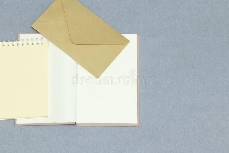 Den öppnade anteckningsboken, gult papper, kuvert på den gråa bakgrunden arkivbilder