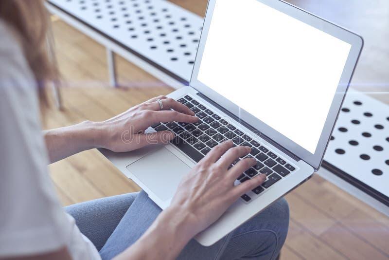 Den öppnade bärbara datorn på kvinna knäa, händer på tangentbordet, utrymme för mallen för designorienteringen för modell Dagslju arkivfoto