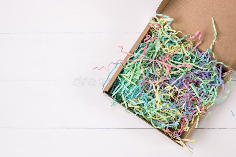 Den öppnade gåvan som postar den kraft asken med färgrikt, rynkar silkespappret inom fotografering för bildbyråer