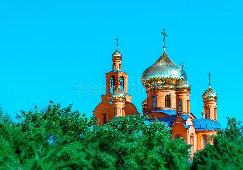 Den östliga kyrkan med guld- kupoler eller kupoler och blå himmel för ortodoxa korsagaints och gröna träd i den Pokrov staden par arkivfoto