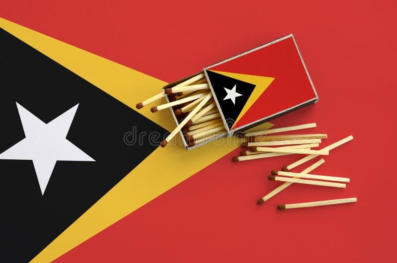 Den Östtimor flaggan visas på en öppen tändsticksask, som flera matcher faller från och lögner på en stor flagga royaltyfri bild