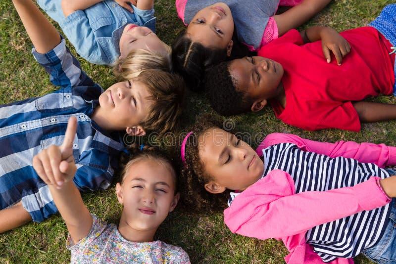 Den över huvudet sikten av barn med armar lyftte att ligga på fält royaltyfri foto