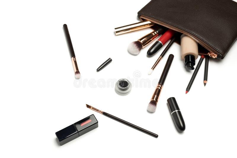 Den över huvudet sikten av utgör produkter som spiller ut ur en brun skönhetsmedelpåse på vit arkivbild