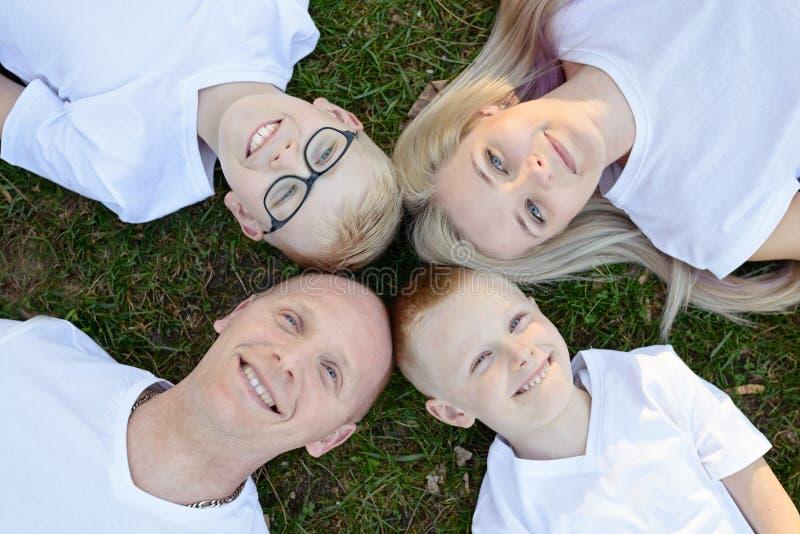 Den över huvudet ståenden på familjen som ligger på gräs parkerar in royaltyfri bild
