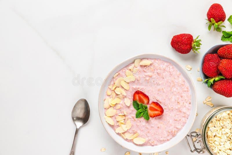 Den över natten jordgubbehavren med den nya bär, mandlar och mintkaramellen i en bunke med en sked på marmorerar tabellen sund fr arkivbilder