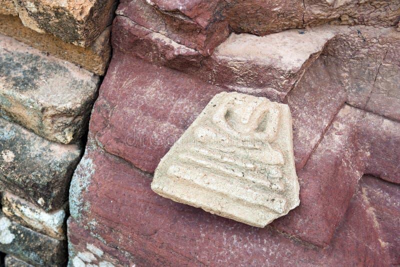 Den övergav brutna Buddhabildamuletten lämnade yttersidan fördärvade sandstenpagoden i templet, nordöstra Thailand arkivbild
