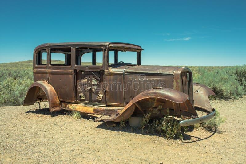 Den övergav rostade antika bilen nära målade öknen på Route 66 arkivbilder