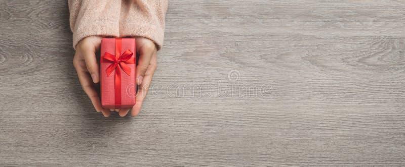 Den översta vyn över kvinnliga händer håller en liten röd presentlåda. royaltyfri fotografi