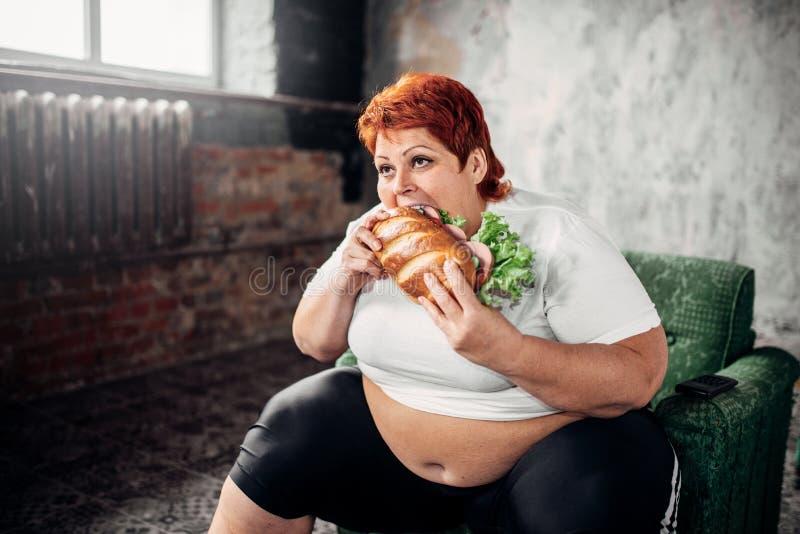 Den överviktiga kvinnan äter smörgåsen som är bulimic royaltyfri fotografi