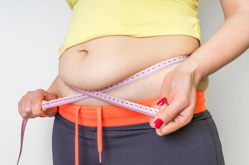 Den överviktiga kvinnan med bandet mäter fett på buken arkivfoto