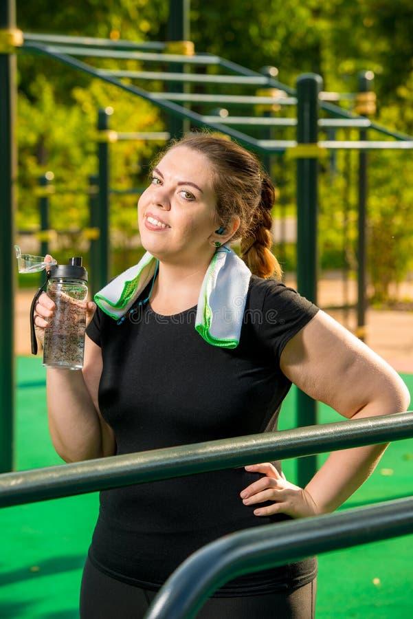 den ?verviktiga kvinnan med en flaska av klart vatten vilar, efter utbilda i, parkerar arkivbilder