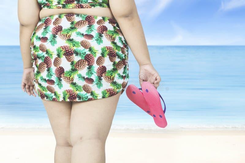 Den överviktiga kvinnan rymmer sandaler på stranden arkivbild