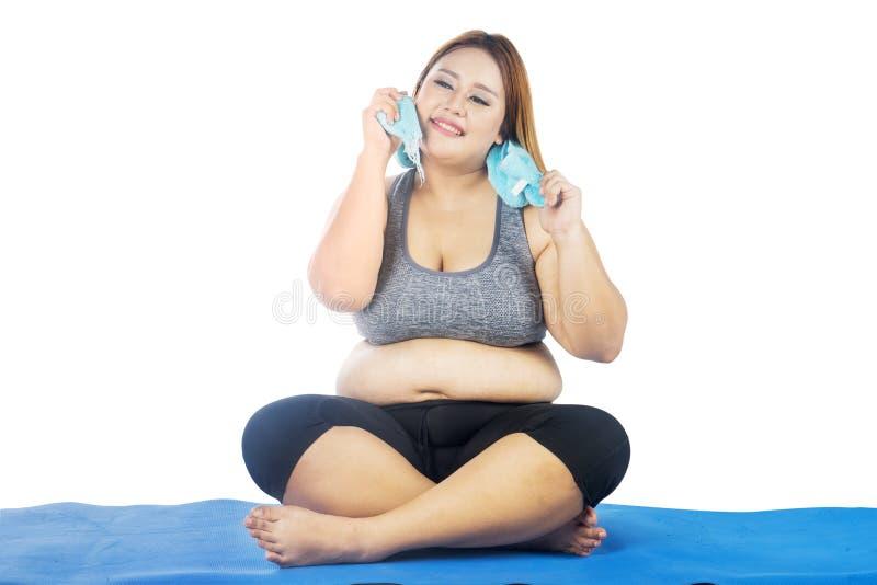 Den överviktiga kvinnan tar en vila på mattt royaltyfri fotografi