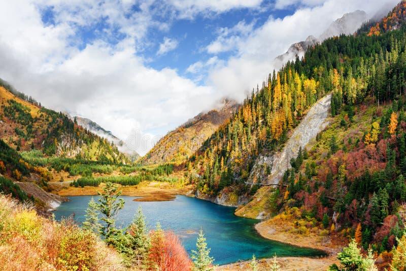 Den övresäsongsbetonade sjön med azurvatten bland berg i dimma arkivfoton
