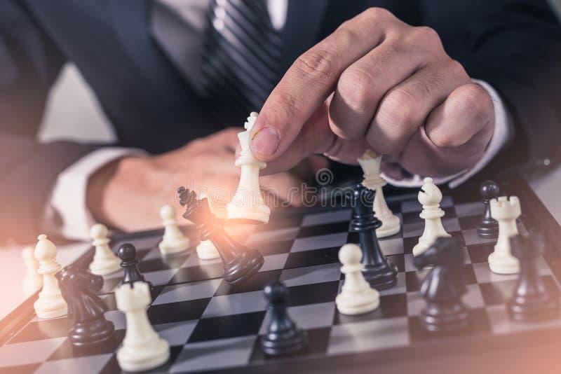 Den abstrakta bilden av affärsmannen tar en schackmatt på schackbrädet under lekarna arkivbilder