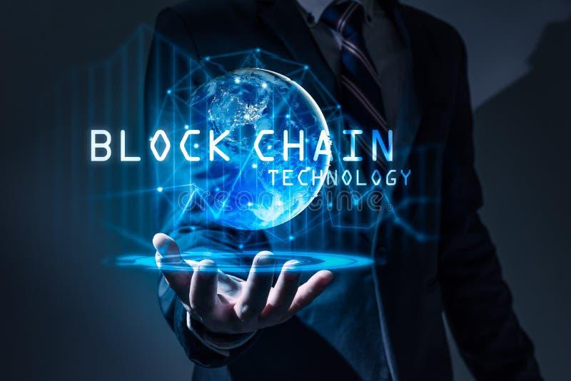Den abstrakta bilden av hållen för affärsmannen blockchainhologrammet förestående och beståndsdelen av denna bild möblerade vid N royaltyfri bild