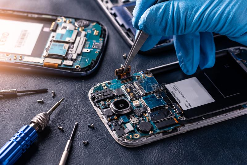 Den abstrakta bilden av teknikeren som monterar inom av smartphonen vid skruvmejseln i labbet arkivbilder