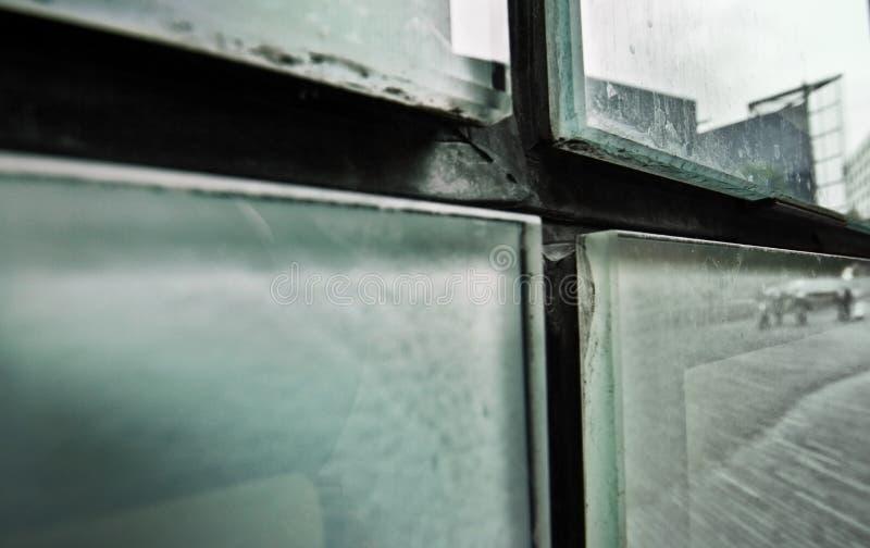 Den abstrakta detaljen av smutsigt glass förser med rutor på sidan av byggnaden royaltyfri bild