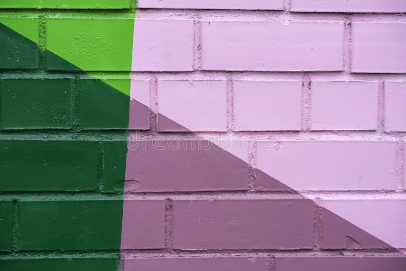 Den abstrakta detaljen av tegelstenväggen med fragmentet av färgrik målarfärg gillar som grafitti Med st?llet f?r din text f?r ba royaltyfri foto