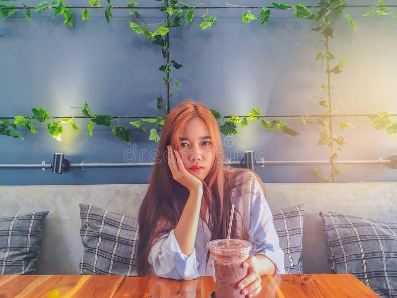 Den abstrakta mjuka fokusen av den unga damen, drink för tonårs- flicka det kalla kaffet i det plast- exponeringsglaset i rummet  royaltyfri foto