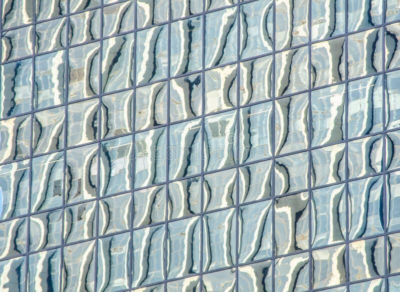 Den abstrakta modellen reflekterar på det glass fönstret av högväxt byggnad royaltyfria bilder